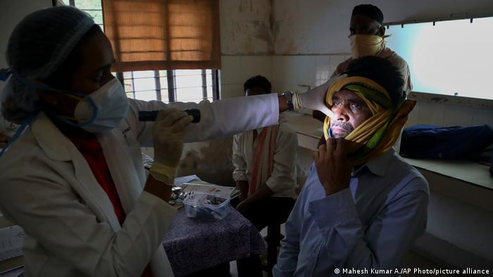 A doctor checks a patient who recovered from COVID-19 but is now infected with